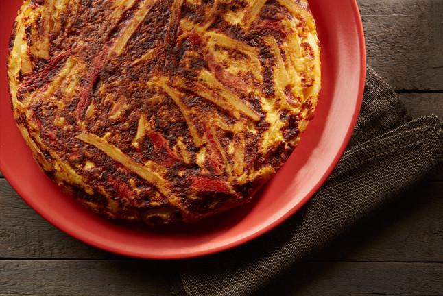 Tortilla de papas con cebollas, pimientos rojos asados y sardo